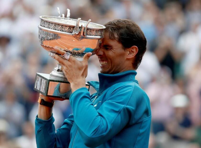 Rafael Nadal of Spain celebrates with the trophy after winning his 11th French Open title against Dominic Thiem of Austria during their men'Äôs final match during the French Open tennis tournament at Roland Garros in Paris, France, 10 June 2018. EFE