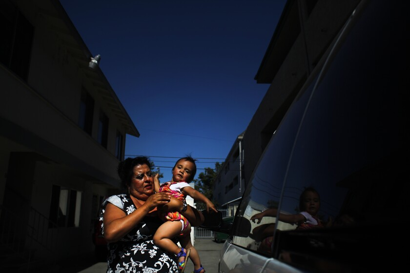 A mother and her child stand outside their apartment in Santa Ana.