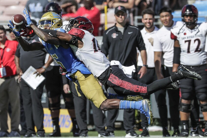 UCLA receiver Jaylen Erwin is challenged by San Diego State cornerback Luq Barcoo.