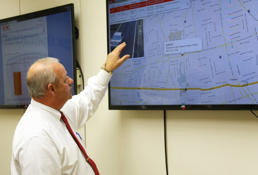 In this Nov. 19, 2015 photo, Freeport Mayor Robert Kennedy demonstrates the village's license plate scanner system at Village Hall in Freeport, N.Y. Since November 2015, the ring of 27 cameras has scanned more than 15.4 million license plates, resulting in 25 people being arrested, 500 cars being i