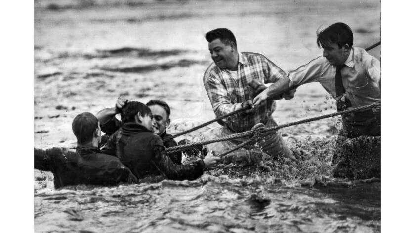 Jan. 23, 1952: Fireman James Hassen lifts Jim Rossetto, 13, by the hair after the boy and fireman John Reeves reach the bank of the Los Angeles River near Glassell.