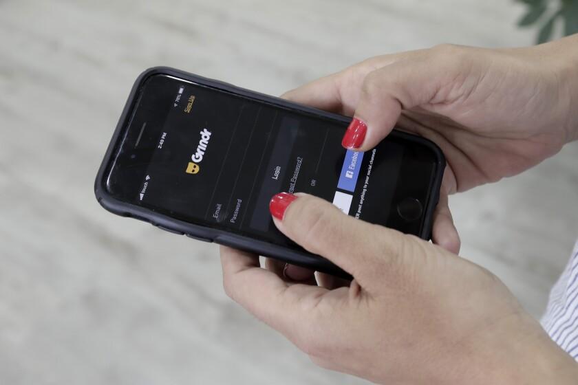 Fotografía de archivo del 29 de mayo de 2019 de una mujer viendo la app Grindr en su celular en Beirut, Líbano. (AP Foto/Hassan Ammar, Archivo)