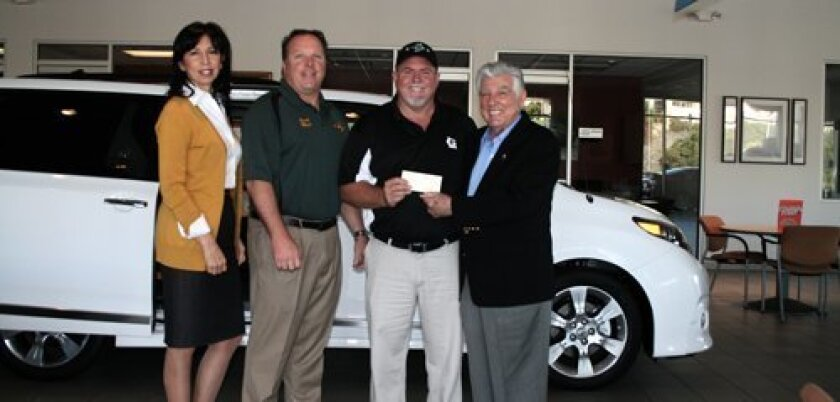 Bob Baker (above, far right) presents the check to Steve Gulley, president of the Lemon Grove Little League.