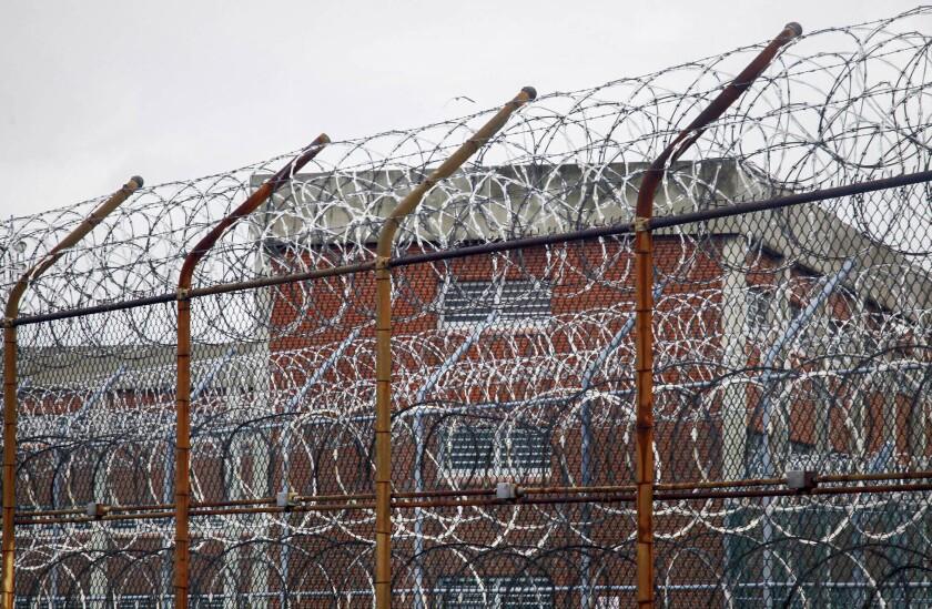 ARCHIVO - Esta foto de archivo del 16 de marzo de 2011 muestra una valla de alambre fuera de los alojamientos de los reclusos en el centro penitenciario neoyorquino de Rikers Island, en Nueva York. El tristemente célebre complejo carcelario de Rikers Island de Nueva York, aquejado de años de abandono, ha entrado en una espiral de turbulencias durante la pandemia de coronavirus. (AP Foto/Bebeto Matthews, Archivo)