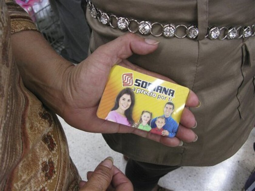 A woman shows her pre-paid gift card while waiting in line at a Soriana supermarket in Mexico City, Tuesday July 3, 2012. Many of the people at the supermarket say they went to redeem pre-paid gift cards they said were given them by the party that won Mexico's presidency and at least a few cardhold