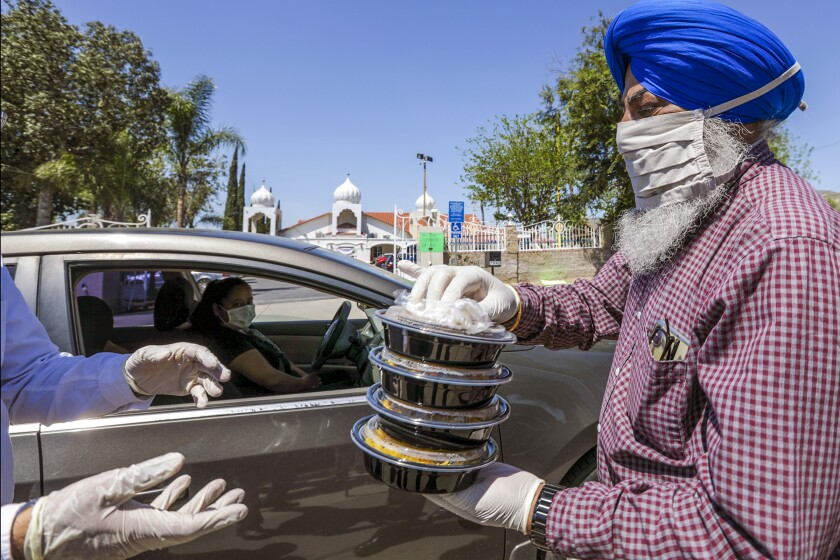 Balwinder Sidhu helps in a food distribution organized by the United Sikh Mission and the city's Sikh community on Thursday at Sikh Gurdwara in Riverside.