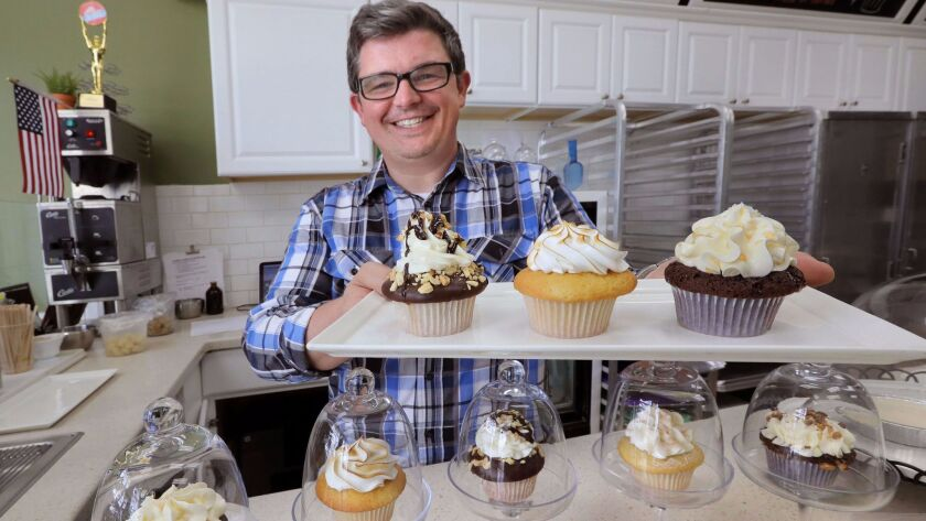 Don Hein, owner of Little Cakes Cupcake Kitchen, holds three of the more popular flavors of cupcakes his business makes.