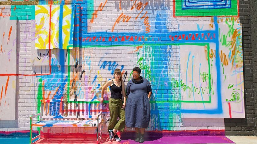 "Sarah Cain, left, and curator Jamillah James, pose in front of Cain's wall painting, ""Now I'm Going"