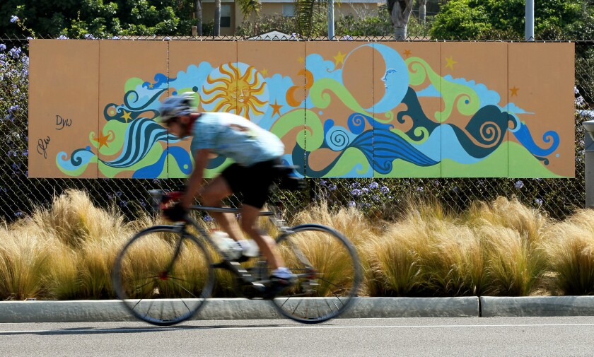 A cyclist heading north on Highway 101 in 2012 passes a work of art mounted on the fence along the Coastal Rail Trail in Solana Beach, north of Lomas Santa Fe Drive.