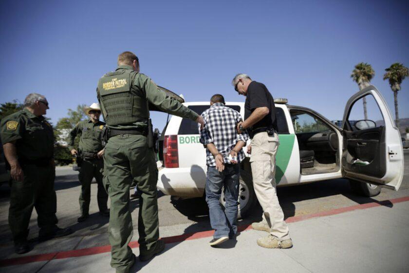 Agentes de la Border Patrolse llevan a una persona indocumentada en San Diego, California.