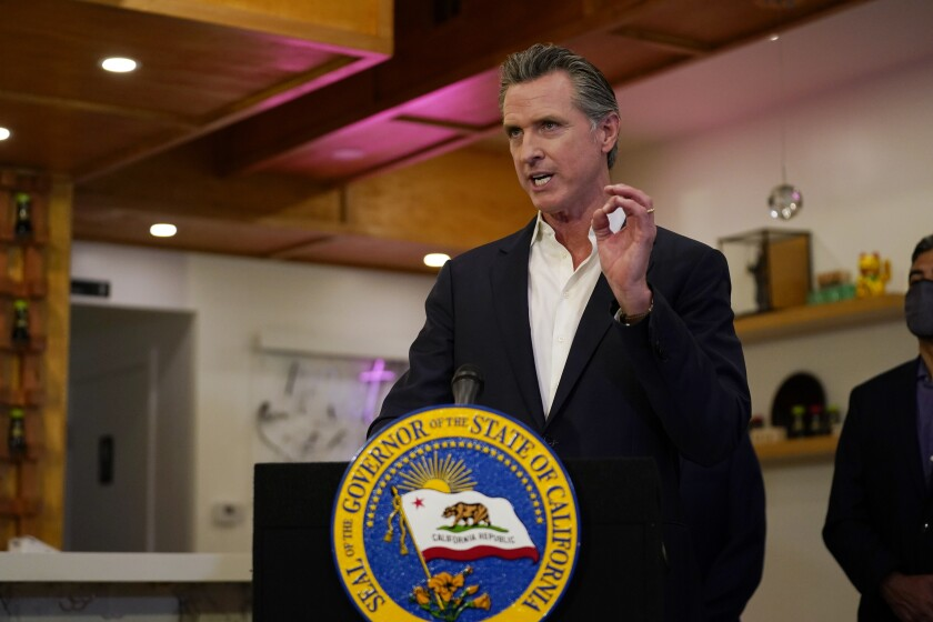Gavin Newsom gestures with his left hand while speaking at a lectern with the seal of the governor of California on it