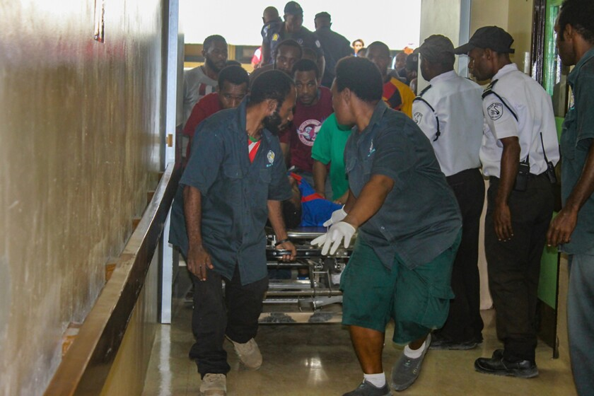 An injured student is rushed to the emergency room at Port Moresby General Hospital on June 8, 2016 in Port Moresby, Papua New Guinea.