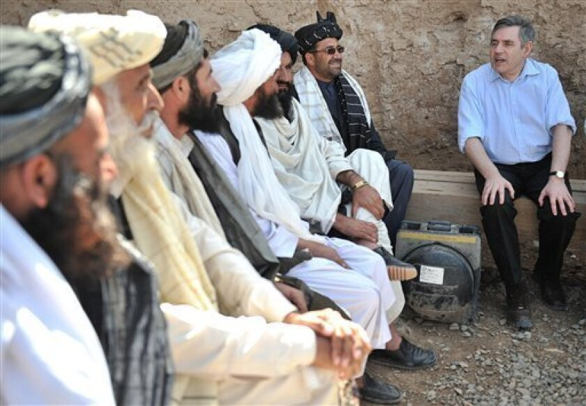 British Prime Minister Gordon Brown (right) talks with Afghan village elders at the Shawqat Forward Operating Base, Lashkar Gah, Helmand Province, Afghanistan. Saturday March 6, 2010. British Prime Minister Gordon Brown is visiting his nation's troops in Afghanistan and promising them 200 new patrol vehicles that can resist roadside bombs more effectively. Brown made an unannounced trip Saturday to Camp Bastion in Helmand province to thank the troops involved in a 3-week-old offensive to wrest control of the town of Marjah from the Taliban. The Press Association news agency says he focused on the battle against homemade bombs and the need to bolster training of the Afghan police force. (AP Photo / Carl De Souza, pa)