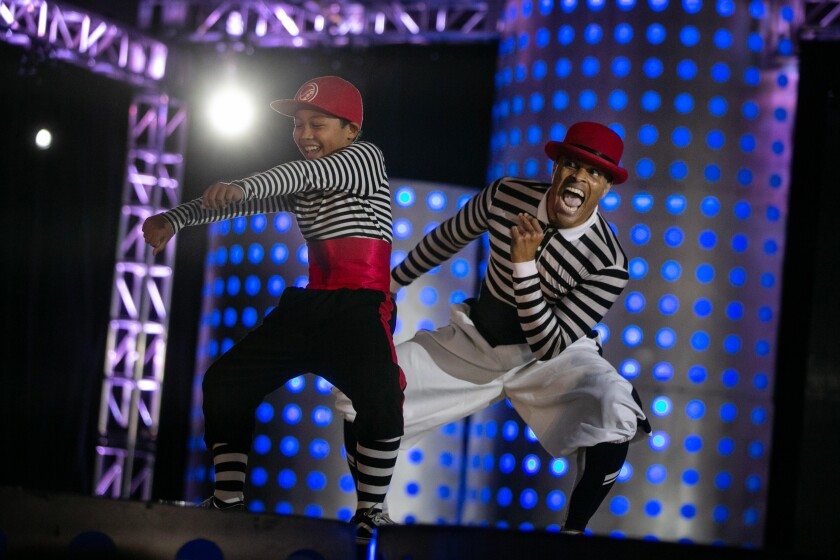 Flomaster and his son Prince onstage in black-and-white striped outfits