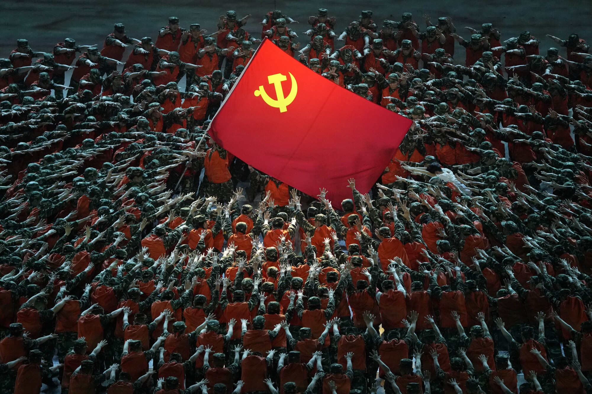 A large red flag with a hammer and sickle symbol is encircled by rows of people wearing red, with arms extended