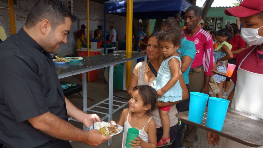 ONE TIME USE - Roman Catholic Fr. Leonardo Mendoza hands out one of the 1,500 meals served daily to
