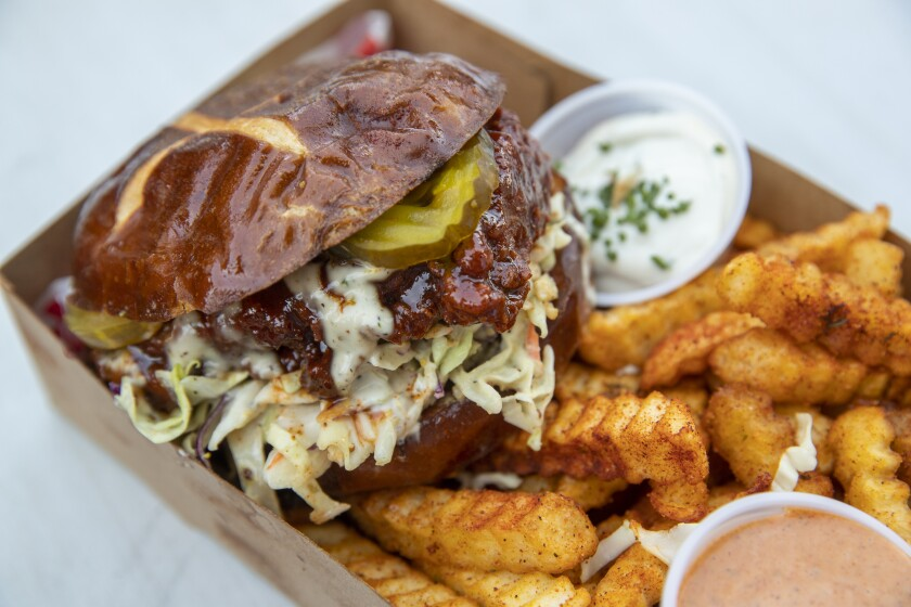 """The Nashville Sando — a """"Southern chick'n patty"""" with pickles, slaw, ranch and spicy dip on a bun —  and crinkle-cut fries from Lettuce Feast."""
