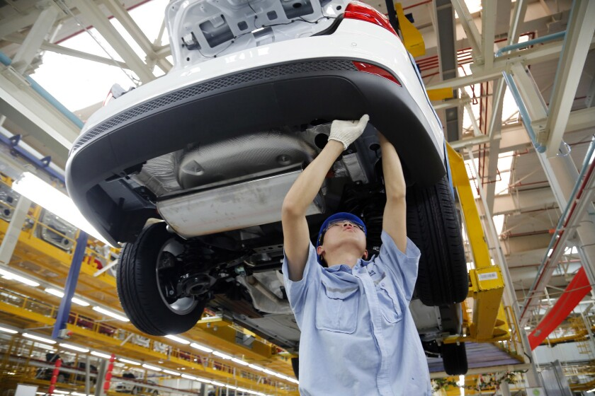 A worker assembles a vehicle on an assembly line at Ford factory in Chongqing, China, on April 16, 2013.