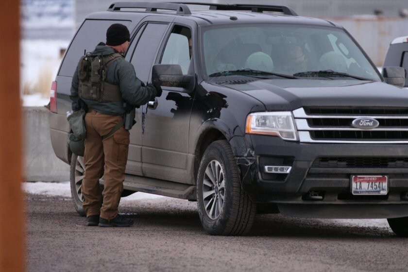 Law enforcement personnel work at the airport, Wednesday, Jan. 27, 2016, in Burns, Ore. Authorities were restricting access on Wednesday to the Malheur National Wildlife Refuge being occupied by an armed group after one of the occupiers was killed during a traffic stop and eight more, including the group's leader Ammon Bundy, were arrested. (Beth Nakamura/The Oregonian via AP) MAGS OUT; TV OUT; NO LOCAL INTERNET; THE MERCURY OUT; WILLAMETTE WEEK OUT; PAMPLIN MEDIA GROUP OUT; MANDATORY CREDIT