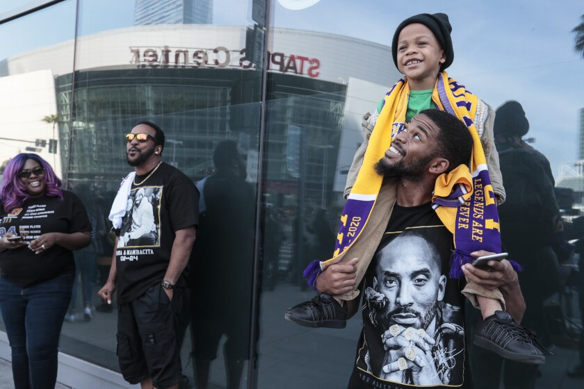 Demond Hewlitt Jr., in a T-shirt with Kobe Bryant's likeness, carries son Demond on his shoulders outside Staples Center.