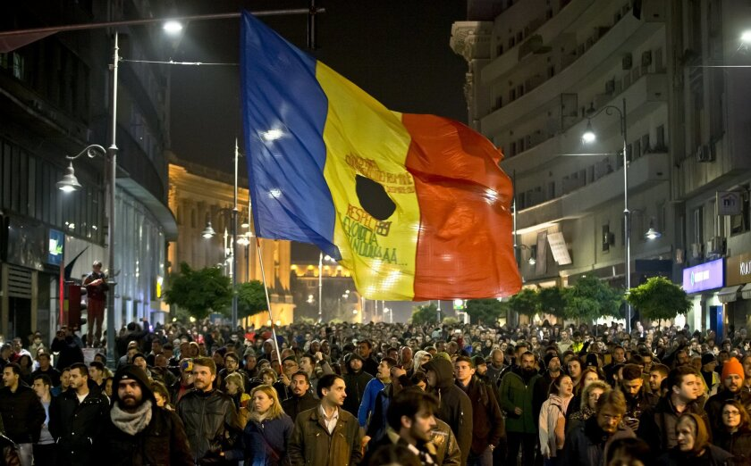 Romanians fill the Calea Victoriei, a main avenue of the Romanian capital, during a large protest in Bucharest, Romania, Tuesday, Nov. 3, 2015. More than 10,000 marched down the city's main boulevards and then massed outside the government offices Tuesday evening calling for the resignation of Prim