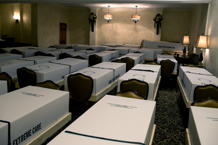 Bodies in boxes in the chapel of a funeral home.