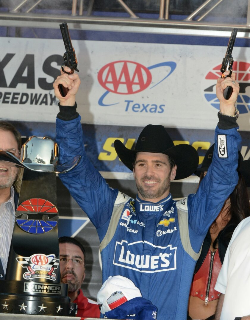 Jimmie Johnson fires pistols in victory lane after winning the NASCAR Sprint Cup Series auto race at Texas Motor Speedway in Fort Worth, Texas, Sunday, Nov. 8, 2015. (AP Photo/Larry Papke)