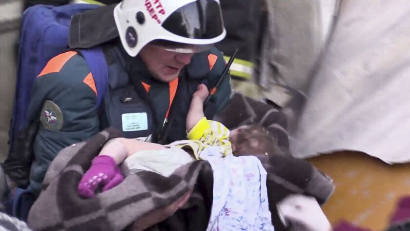 A rescuer carries a baby boy found alive amid the debris of a collapsed apartment building in Magnitogorsk, Russia. The child's recovery prospects are unclear.