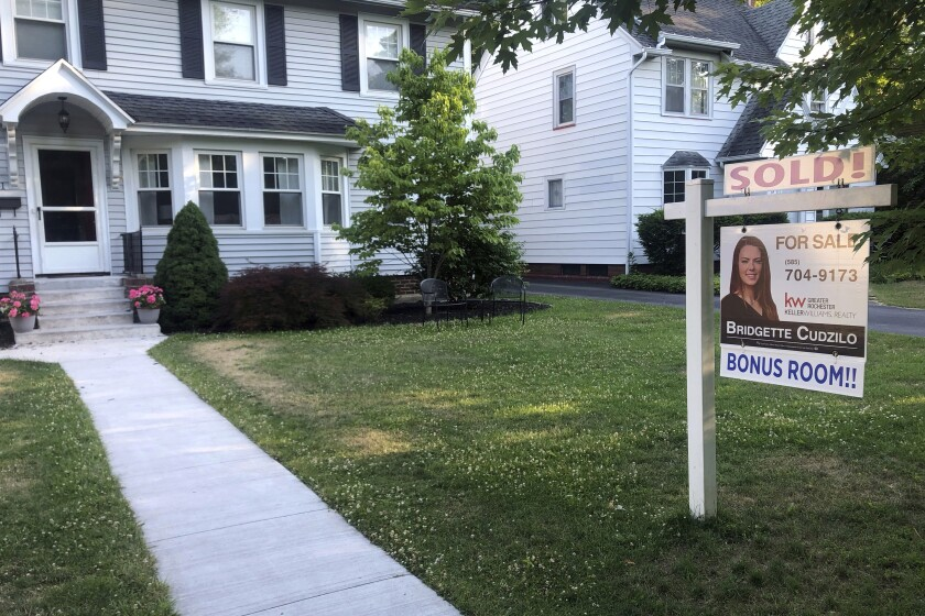 A sold sign hangs in front of a house in Brighton, New York, on Saturday, July 4, 2020. Long-term U.S. mortgage rates fell the first week of July with the benchmark 30-year home loan hitting its lowest level ever. (AP Photo/Ted Shaffrey)