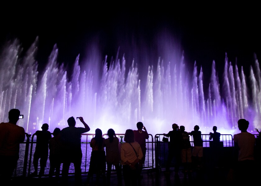 People watch a fountain show outside in Okada Manila in Entertainment City, Paranaque, Philippines,