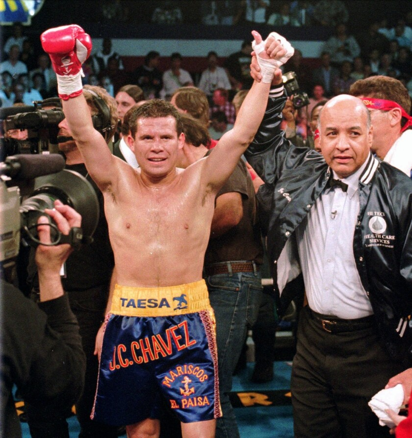 This Feb. 9, 1996, file photo shows WBC junior welterweight champion Julio Cesar Chavez, left, celebrating his victory over Scott Walker as referee Joe Cortez signals him the winner of their 10-round non-title bout in Las Vegas. Chavez and referee Cortez were selected Tuesday, Dec. 10, 2010, for induction into the International Boxing Hall of Fame and Museum.
