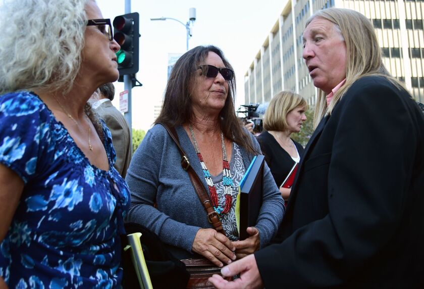 """Michael Skidmore, right, talks to Janet Wolfe, left, and Marla Randall, sisters of rock musician Randy Wolfe, aka Randy California, outside the federal courthouse following the jury's verdict that Led Zeppelin did not steal portions of Wolfe's song """"Taurus."""""""