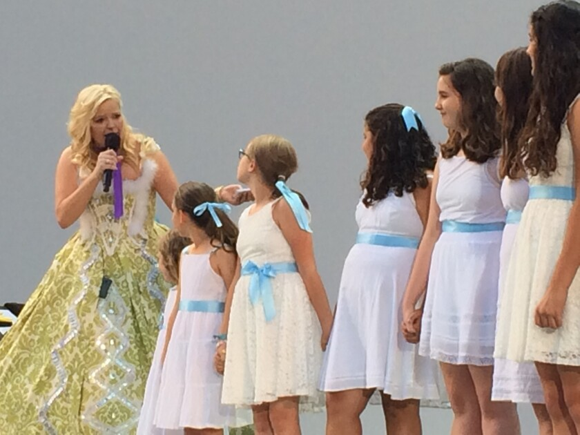 "Pre-show host Melissa Peterman with girls in white dresses with blue satin sashes at the Hollywood Bowl's ""Sound of Music"" sing-along on Friday."