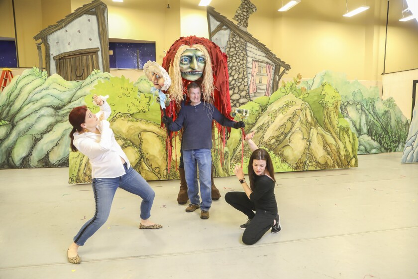 """During a rehearsal of San Diego Opera's """"Hansel and Gretel"""" cast members Blythe Gaissert, left, as Hansel, Joel Sorensen as the witch and Sara Gartland as Gretel pose for photos for the production, which will open Feb. 8 at the San Diego Civic Theatre. Not pictured is show designer Judd Palmer, who is operating the back portion of the Witch puppet."""