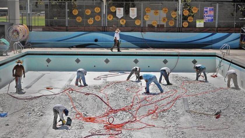 Workers break up the floor of the pool at La Cañada High School in 2014.