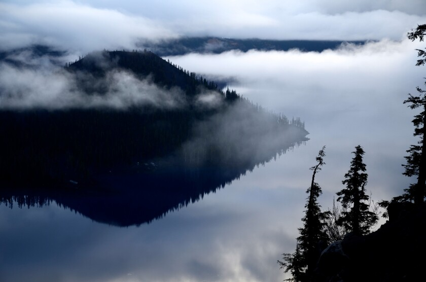 Wizard Island sits near the edge of famously blue Crater Lake in Oregon. The Cleetwood Trail, on the far caldera slope, hidden by mist, is the only way down to water's edge, and it's only open in warmer months.