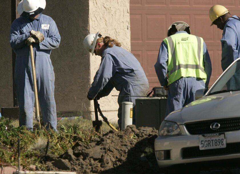In a file photo, San Diego Gas and Electric works on a natural gas line to shut at a home in Mira Mesa. According to SDG&E numbers, ratepayers are paying slightly less this year than last year.