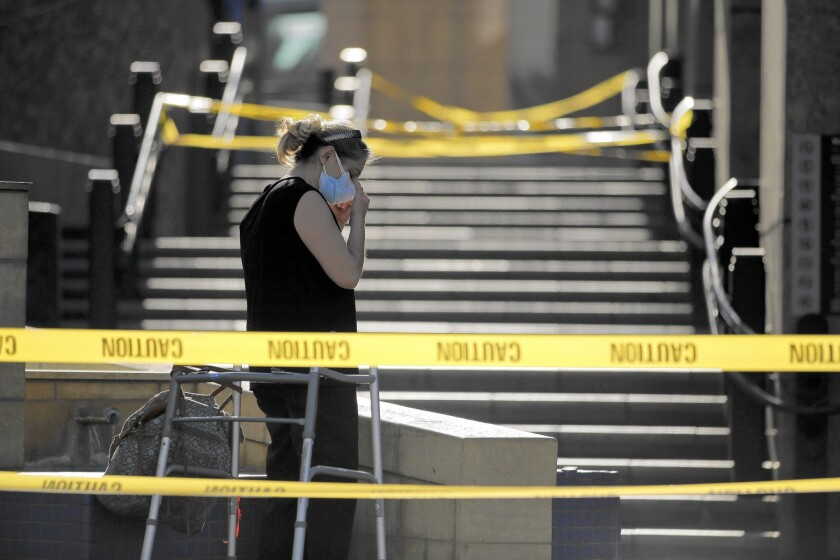 A woman adjusts her mask outside Union Station's Patsaouras Plaza, which was closed off Friday when a FlyAway passenger from Nigeria complained of nausea.