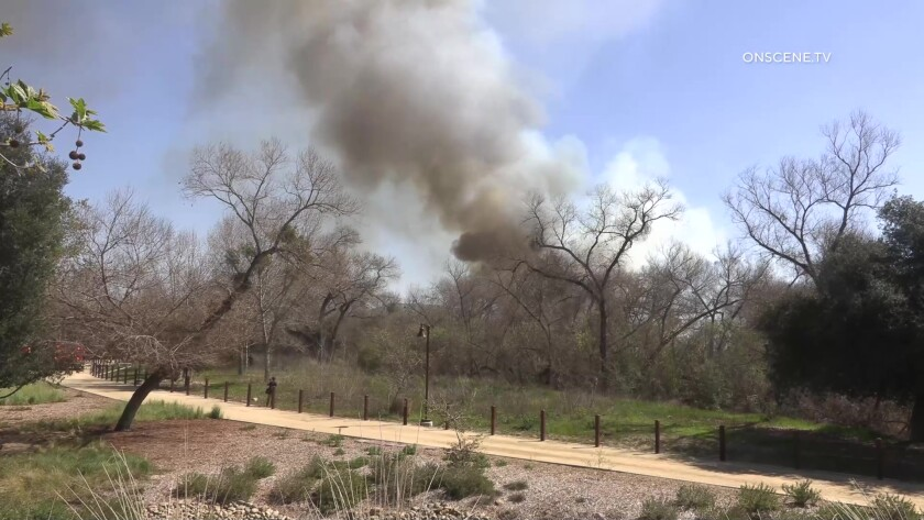Smoke rises from fire in a riverbed by Carlton Hills Boulevard