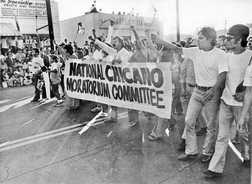 "Young Chicanos march in East Los Angeles on Aug. 29, 1970. Their sign says ""Chicano Moratorium Committee."""