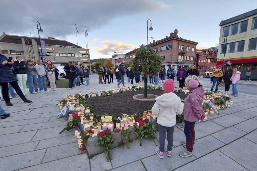 People gather around flowers and candles after a man killed several people on Wednesday afternoon, in Kongsberg, Norway, Thursday, Oct. 14, 2021. The bow-and-arrow rampage by a man who killed five people in a small town near Norway's capital appeared to be a terrorist act, authorities said Thursday, a bizarre and shocking attack in a Scandinavian country where violent crime is rare. Police identified the attacker as Espen Andersen Braathen, a 37-year-old Danish citizen, who was arrested on the street Wednesday night. (AP Photo/Pal Nordseth)