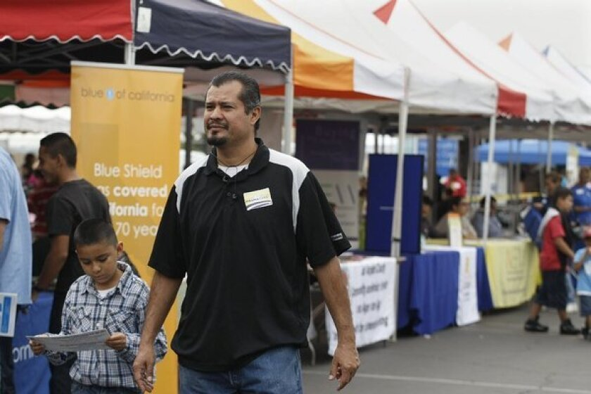 Luis Ramos, with his son Jacob, sought information on the Affordable Care Act last month at the East Los Angeles Health Fair.