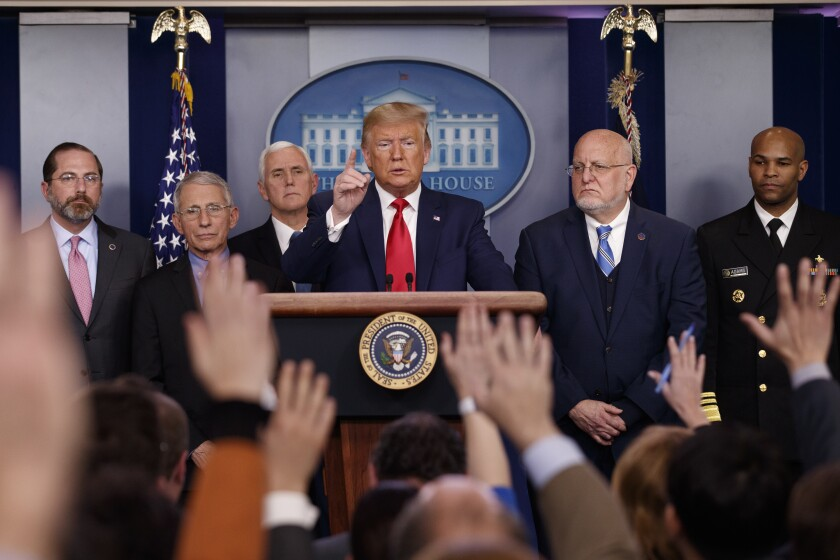 On Feb. 29 President Trump is in the press briefing room at the White House while surrounded by officials.