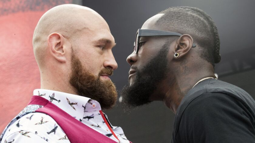 Tyson Fury, left, and Deontay Wilder face off during a news conference in New York.