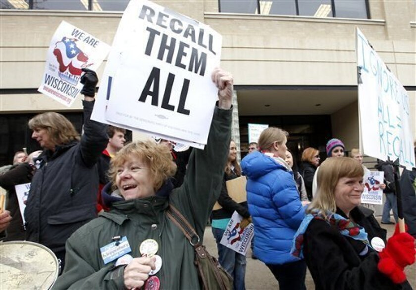 FILE -This April 1, 2011 file photo shows Chris Taylor, left, and Peppi Elder, right, joining demonstrators calling for the recall of State Sen. Dan Kapanke, R-LaCrosse, outside the Wisconsin Government Accountability Board in Madison, Wis. Nearly a month after the Wisconsin standoff over union rights ended, some of the fervor from that debate has shifted to recall efforts targeting lawmakers in both parties _ Republicans who voted to cut back collective bargaining and Democrats who fled the state to try to stop them. (AP Photo/Wisconsin State Journal, John Hart, File)