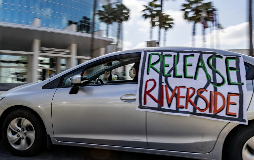 """A car with a """"release Riverside"""" sign on it"""