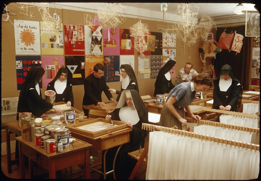 Nuns and a priest work with art materials in a printing studio lined with colorful works