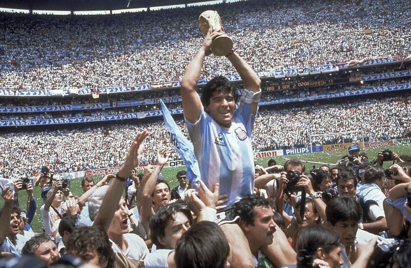 Diego Maradona holds up his team's trophy after Argentina's 3-2 victory over West Germany at the World Cup final in 1986.