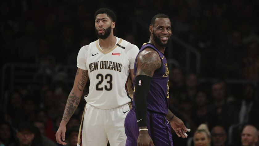 Lakers' LeBron James, right, smiles as he walks past New Orleans Pelicans' Anthony Davis during the first half.