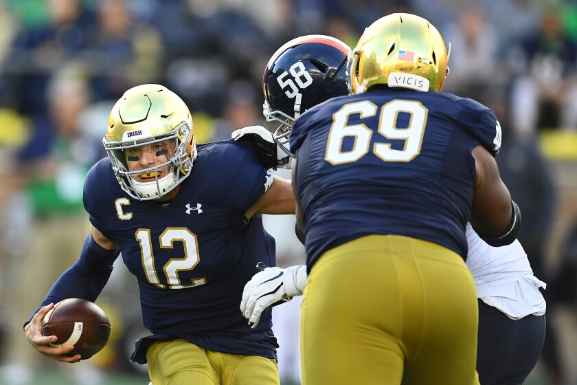 Notre Dame quarterback Ian Book (12) tried to evade Virginia defender Eli Hanback (58) during the second half at Notre Dame Stadium on Sept. 28, 2019 in South Bend, Ind.
